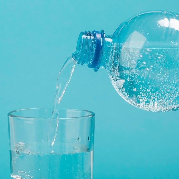 Vista frontal despejando água com gás em um copo Foto Premium