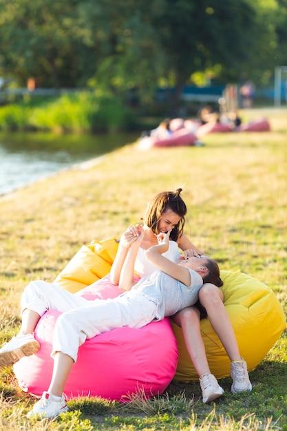 Vista frontal despreocupada amigos em pufes coloridos Foto gratuita