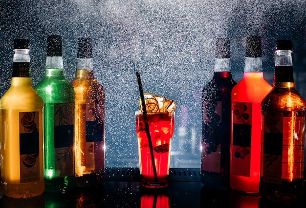Vista frontal diferentes bebidas coloridas dentro de garrafas Foto gratuita