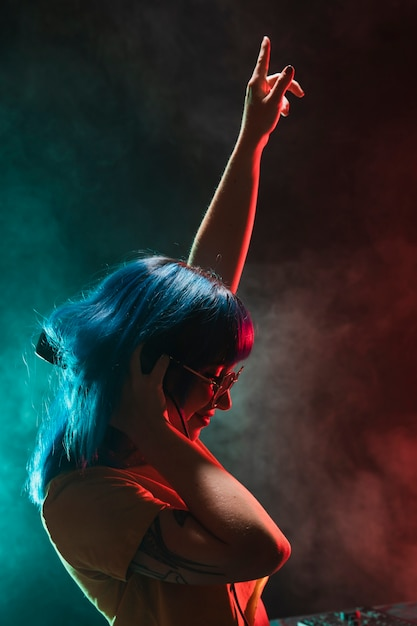 Vista frontal dj feminino com a mão levantada Foto gratuita