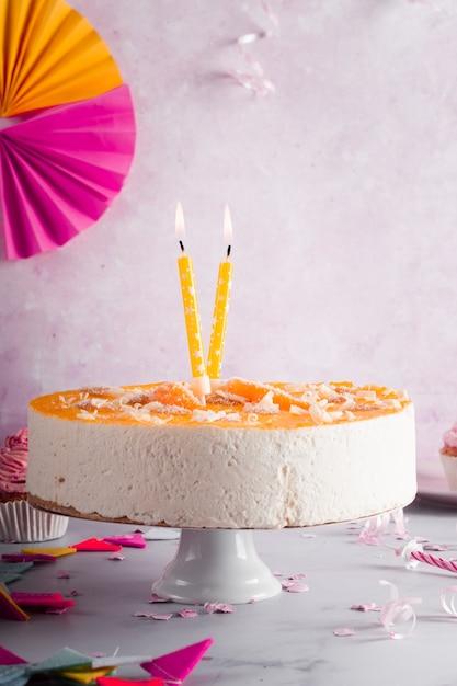 Vista frontal do bolo de aniversário com velas acesas Foto gratuita
