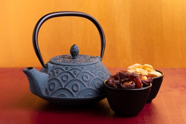 Vista frontal do bule e iguarias para o ano novo chinês Foto gratuita