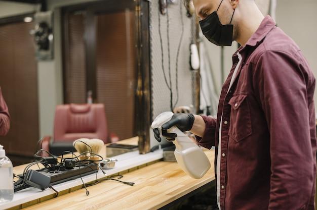 Vista frontal do cabeleireiro limpando a mesa Foto gratuita