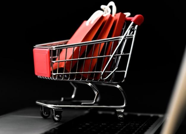 Vista frontal do carrinho de compras da cyber segunda-feira com sacolas Foto gratuita