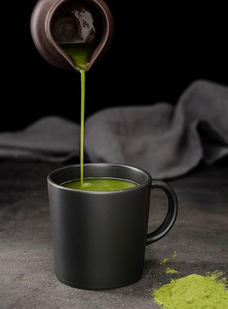 Vista frontal do chá matcha derramado em copo Foto Premium