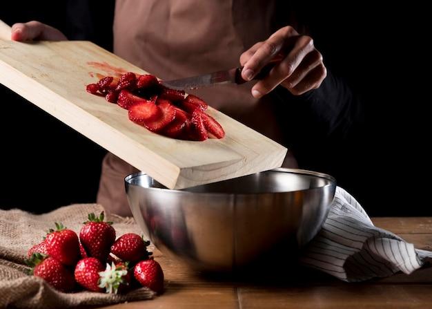 Vista frontal do chef adicionando morangos picados na tigela Foto gratuita