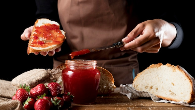 Vista frontal do chef espalhando geléia de morango no pão Foto gratuita