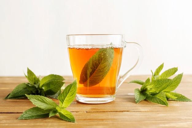 Vista frontal do conceito de chá de ervas na mesa de madeira Foto Premium