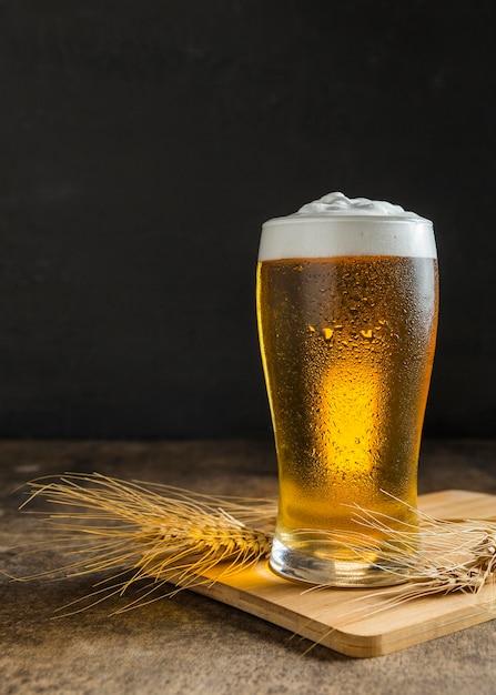 Vista frontal do copo de cerveja com trigo Foto Premium