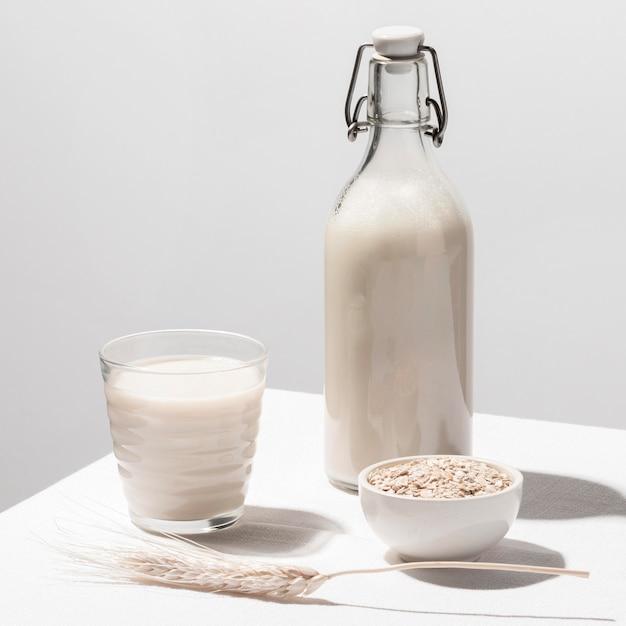 Vista frontal do copo de leite com garrafa e aveia Foto gratuita