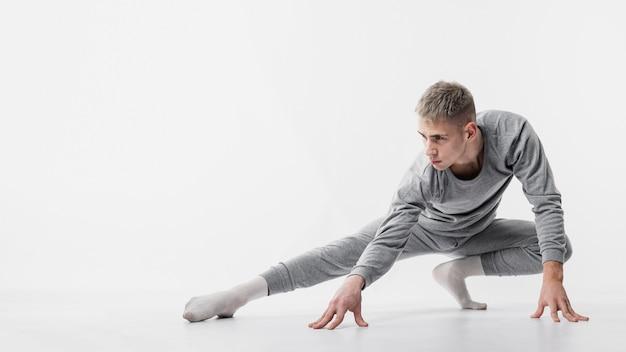 Vista frontal do dançarino masculino em agasalho e meias posando enquanto dança Foto gratuita