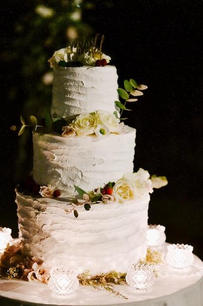Vista frontal do delicioso bolo de casamento cremoso, decorado com eucalipto e rosas brancas em cima da mesa à noite Foto gratuita