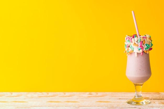 Vista frontal do delicioso milkshake em fundo amarelo Foto gratuita