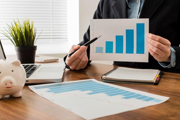 Vista frontal do empresário segurando um gráfico de crescimento Foto gratuita
