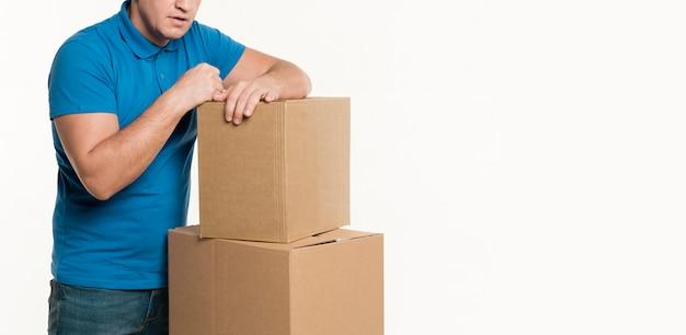 Vista frontal do entregador e caixas de papelão Foto gratuita