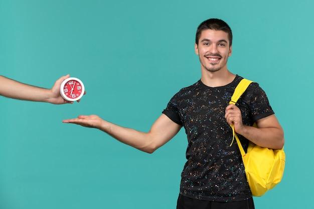 Vista frontal do estudante do sexo masculino na mochila de camiseta amarela escura posando e sorrindo na parede azul clara Foto gratuita