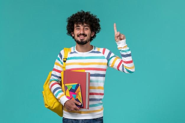 Vista frontal do estudante do sexo masculino usando mochila amarela segurando arquivos e o caderno na parede azul Foto gratuita