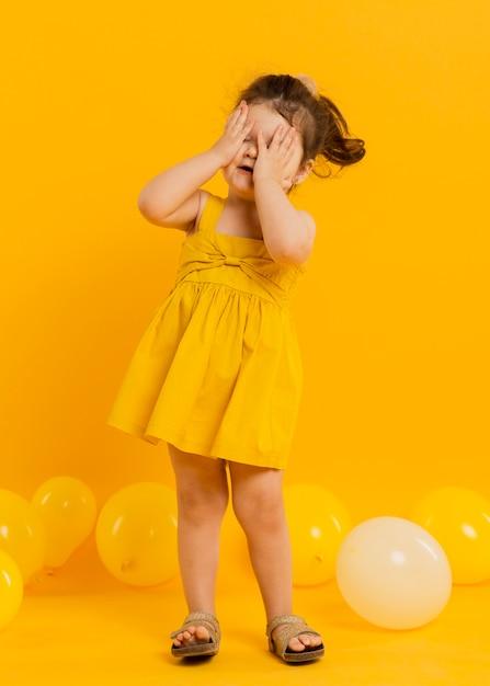 Vista frontal do filho bonito posando com balões Foto gratuita