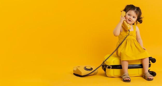 Vista frontal do filho bonito posando com telefone e bagagem Foto gratuita