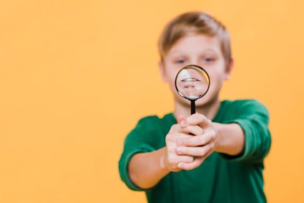 Vista frontal do garoto segurando a lupa Foto gratuita