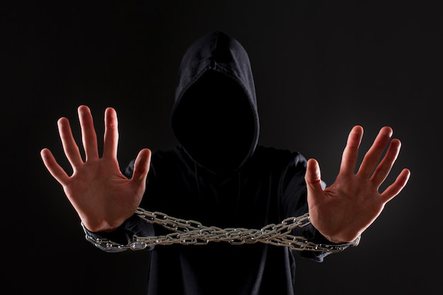 Vista frontal do hacker masculino com corrente de metal em volta das mãos Foto gratuita