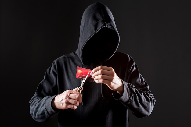 Vista frontal do hacker masculino, corte o cartão de crédito com tesoura Foto gratuita