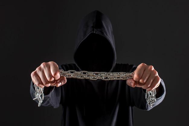 Vista frontal do hacker masculino segurando a corrente de metal nas mãos Foto gratuita