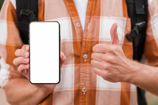 Vista frontal do homem com a mochila segurando o smartphone e dando sinal de positivo Foto gratuita