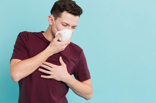 Vista frontal do homem com coronavírus apresentando sintomas Foto gratuita