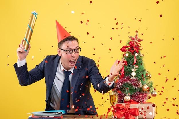 Vista frontal do homem de negócios segurando o popper de festa em pé atrás da mesa perto da árvore de natal e presentes em amarelo Foto gratuita