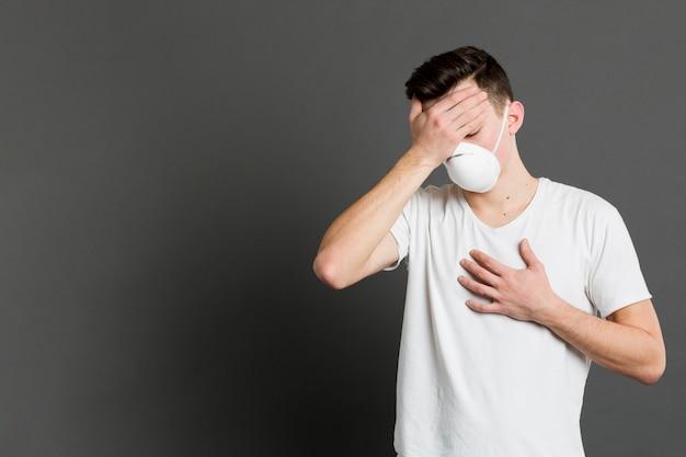 Vista frontal do homem doente, apresentando sintomas de coronavírus Foto gratuita