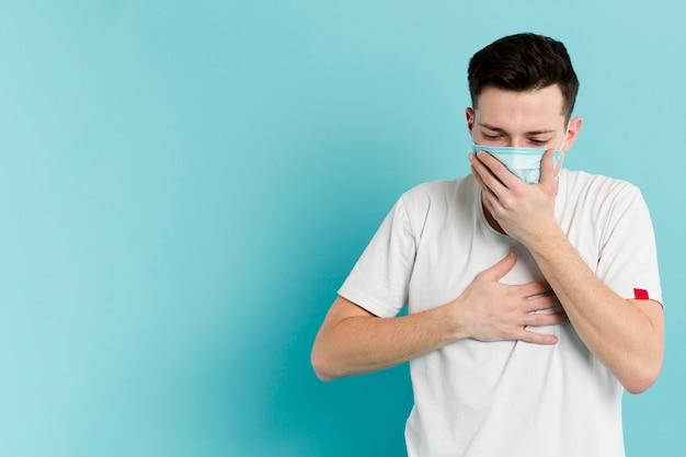 Vista frontal do homem doente, tossindo enquanto usava uma máscara médica Foto Premium