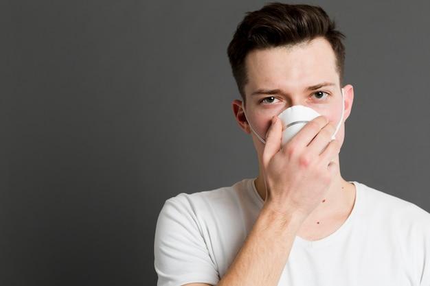 Vista frontal do homem doente, vestindo uma máscara médica Foto gratuita