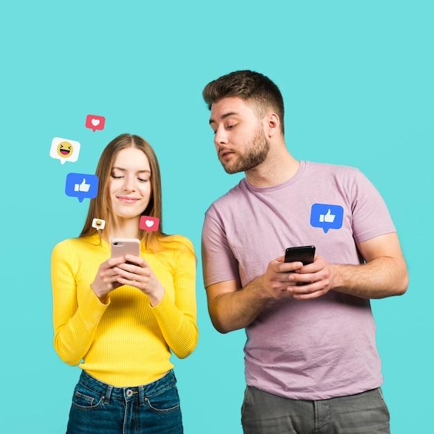 Vista frontal do homem e da mulher olhando para reações de aplicação Foto gratuita