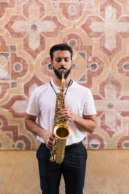 Vista frontal do homem em pé tocando o saxofone com fundo geométrico Foto gratuita