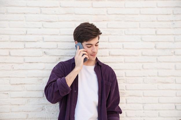 Vista frontal do homem falando no smartphone Foto gratuita