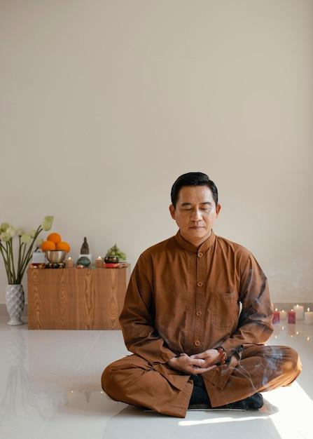 Vista frontal do homem meditando com espaço de cópia e incenso Foto gratuita