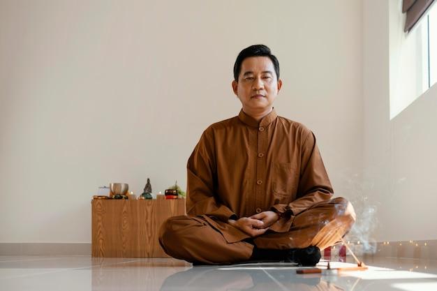 Vista frontal do homem meditando Foto gratuita