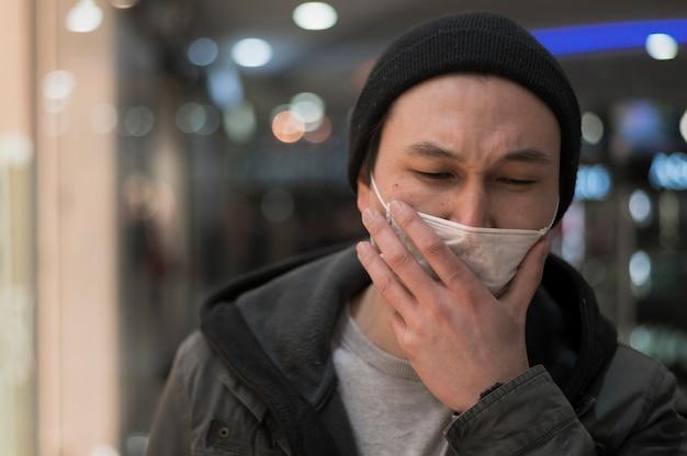 Vista frontal do homem no shopping tossindo em máscara médica Foto gratuita