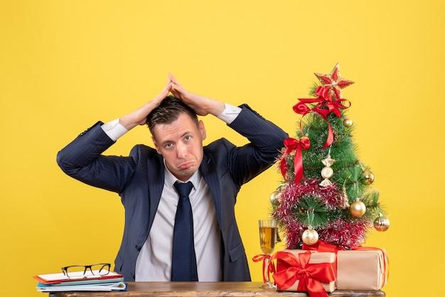 Vista frontal do homem sem alegria fazendo telhado da casa com as mãos, sentado à mesa perto da árvore de natal e presentes em amarelo Foto gratuita
