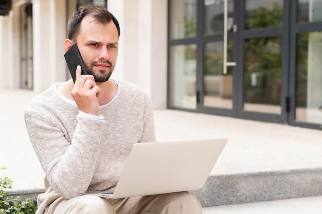 Vista frontal do homem trabalhando no laptop ao ar livre Foto gratuita