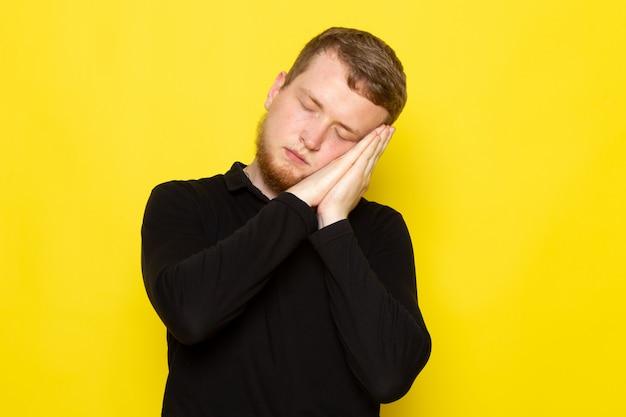 Vista frontal do jovem de camisa preta, posando com gesto a dormir Foto gratuita