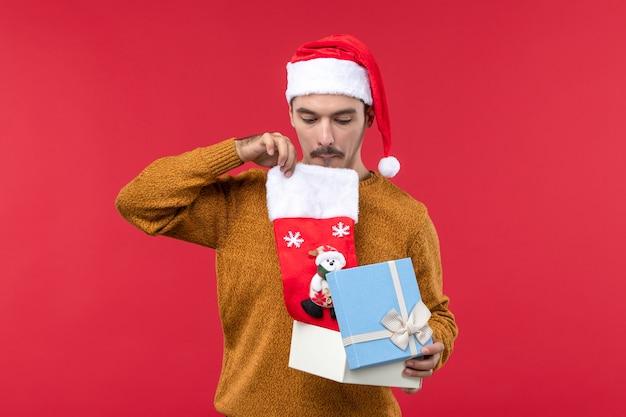 Vista frontal do jovem tirando a meia de natal da caixa na parede vermelha Foto gratuita