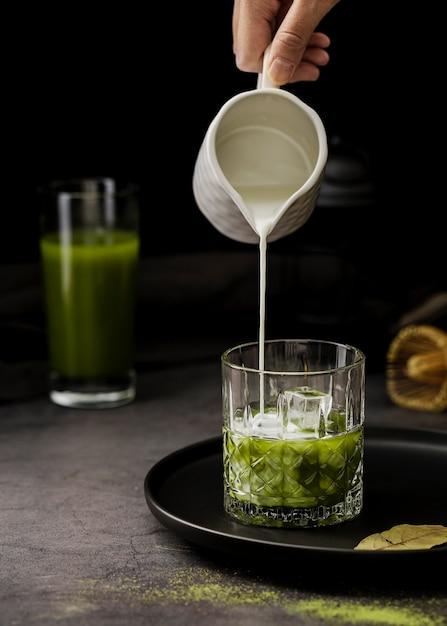 Vista frontal do leite derramado no copo de chá matcha com cubos de gelo Foto Premium