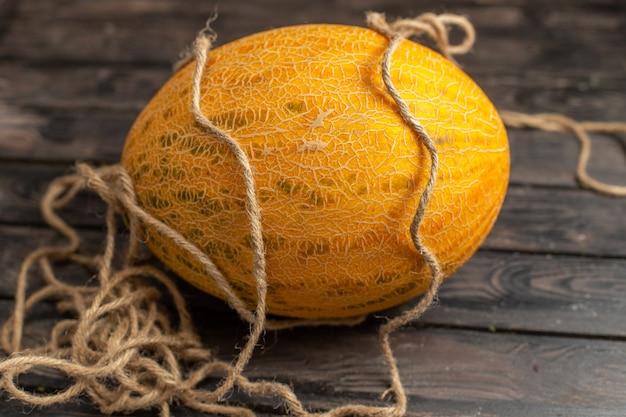 Vista frontal do melão maduro inteiro laranja com cordas no fundo marrom rústico Foto gratuita