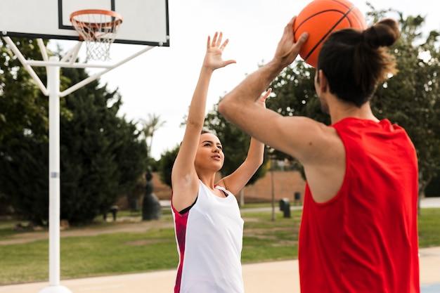 Vista frontal do menino e menina jogando basquete Foto gratuita