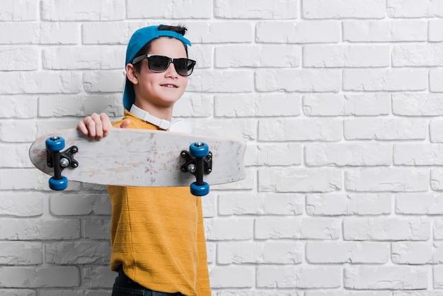 Vista frontal do menino moderno com skate Foto gratuita