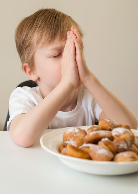 Vista frontal do menino rezando antes de comer Foto gratuita