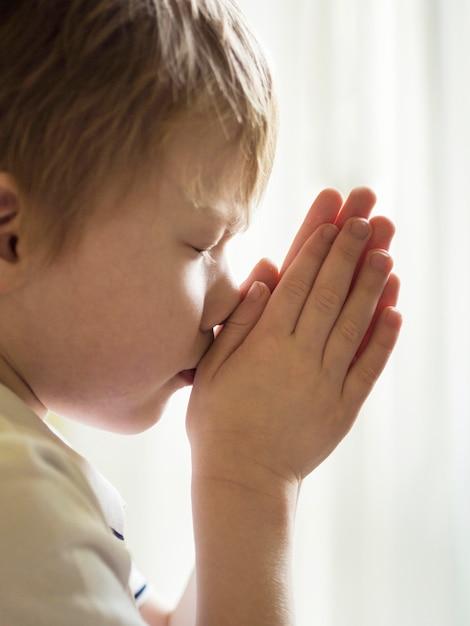 Vista frontal do menino rezando Foto gratuita