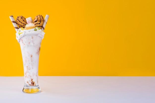 Vista frontal do milk shake com espaço amarelo de fundo e cópia Foto gratuita
